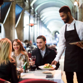 Positive young black waiter serving terrace restaurant guests at table.Focus on the man